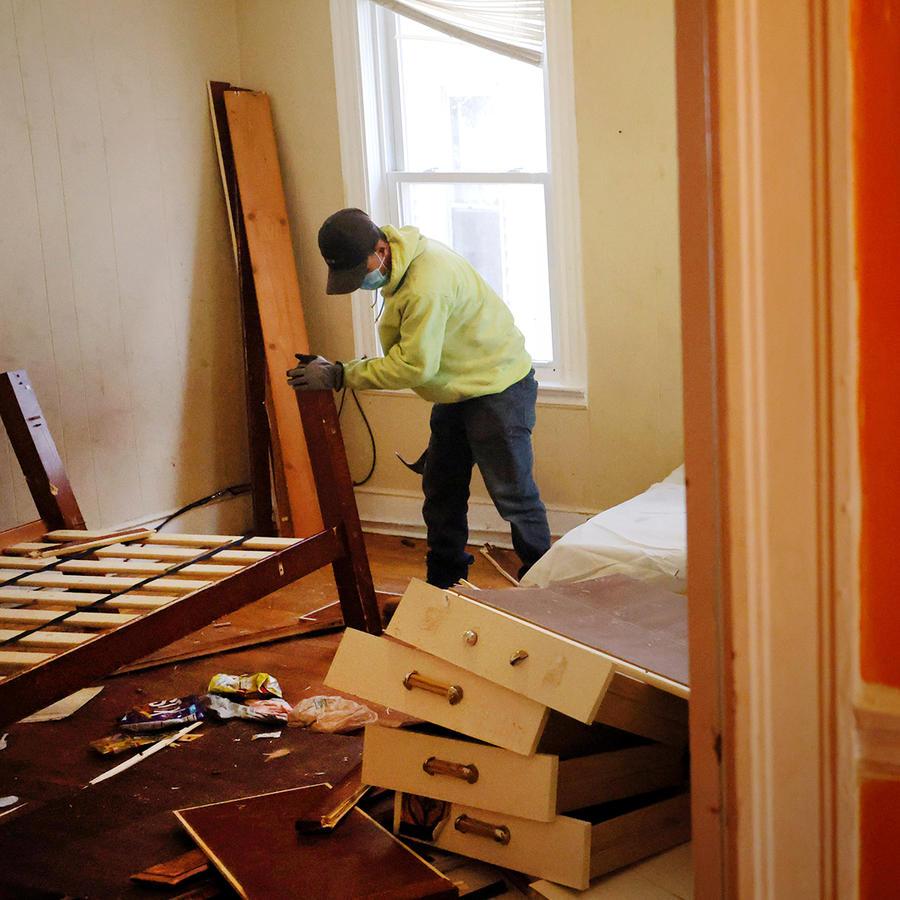 Varios trabajadores rompen los muebles que dejó un inquilino desalojado después de un aviso de 48 horas por violar los términos de su contrato de alquiler en Chelsea, Massachusetts, 29 de marzo de 2021.