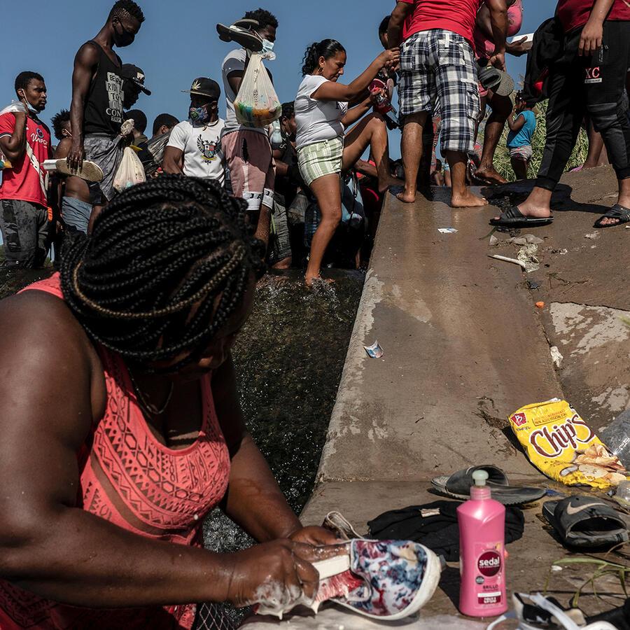 Migrantes que buscan asilo en Estados Unidos caminan por el río Grande cerca del Puente Internacional en la frontera con México mientras esperan ser procesados, en Del Rio, Texas, 16 de septiembre de 2021.