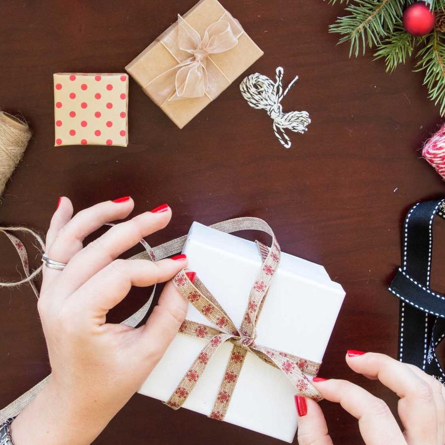 Mujer haciendo lazo con cinta de navidad