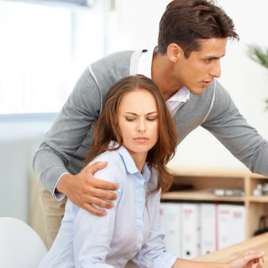 Hombre tocando a una mujer en el trabajo