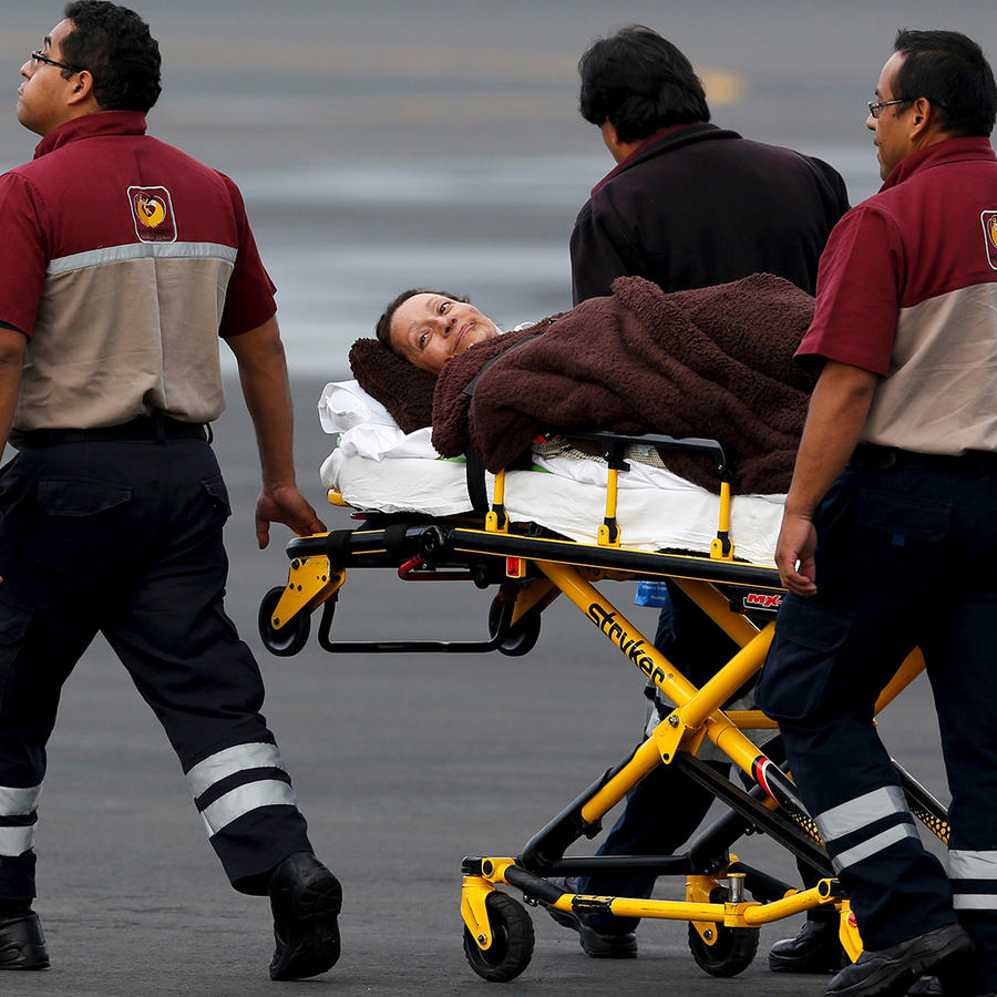 Paramedics wheel a Mexican tourist, who was injured during an attack in Egypt, toward a helicopter after his arrival to the presidential hangar in Mexico City