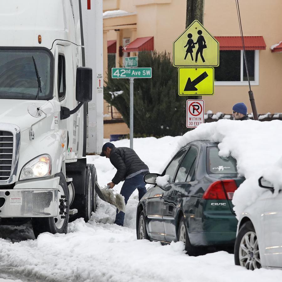 El conductor de un camión intenta retirar la nieve de su vehículo el 12 de febrero de 2019 en Seattle
