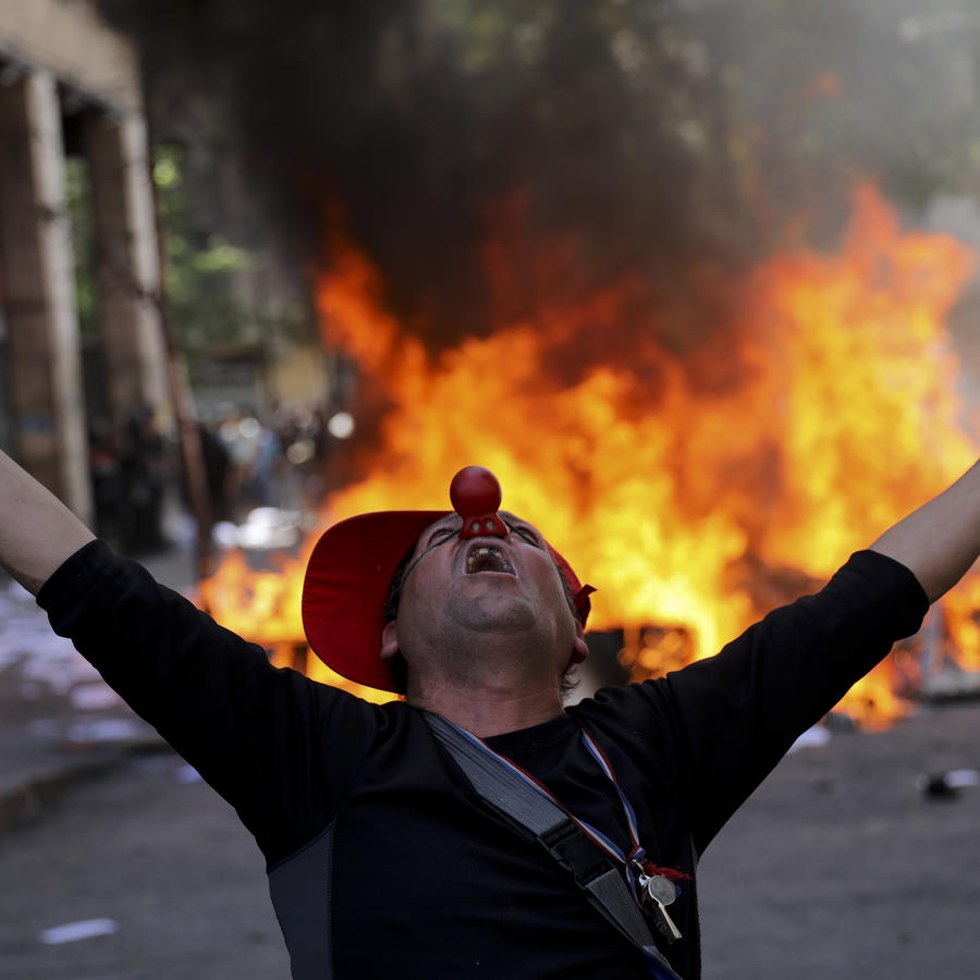 An anti-government demonstrator screams in font of a burning barricade in Santiago, Chile.