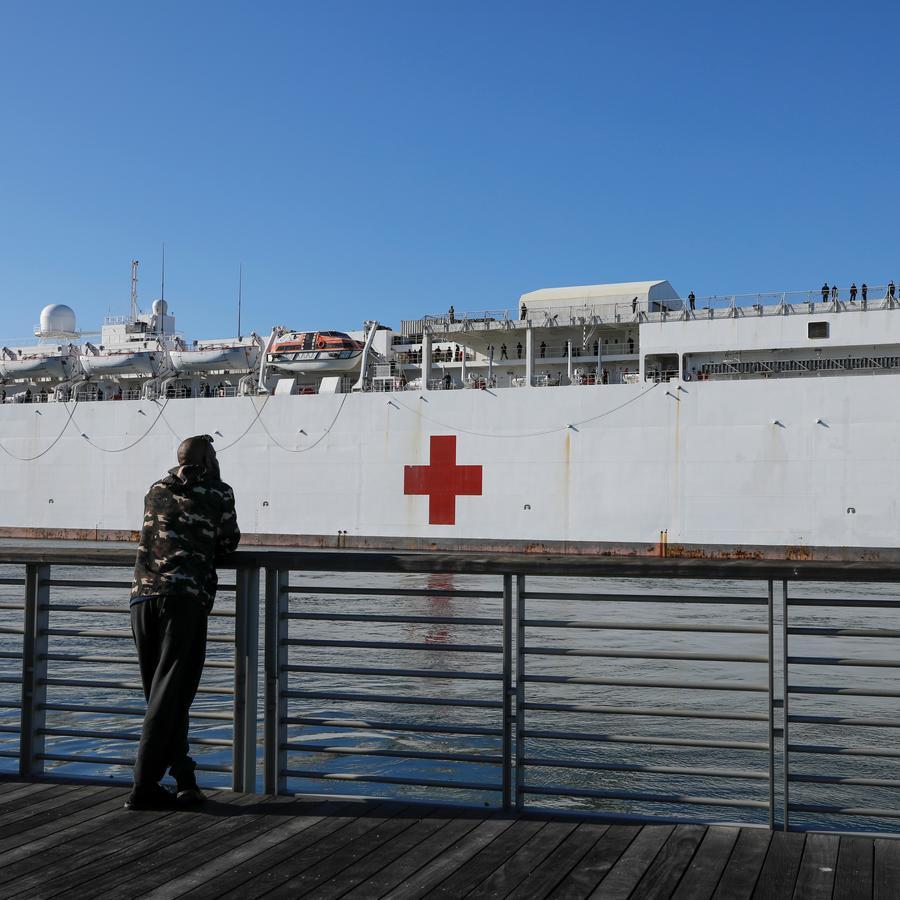 Un hombre observa cómo el buque hospital USNS Mercy llega al puerto de Los Ángeles para ayudar a las instalaciones médicas del área durante el brote de la enfermedad por coronavirus (COVID-19) en San Pedro, California, EE. UU.