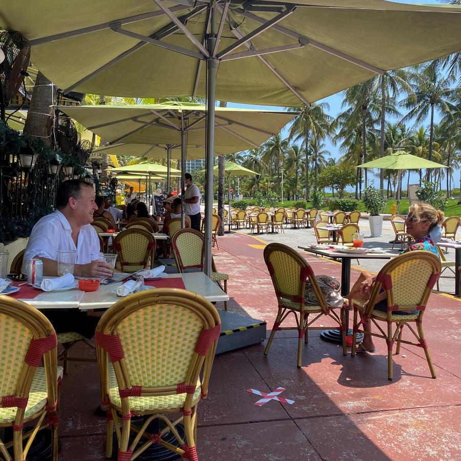 La gente se sienta en el restaurante Il Giardino mientras los restaurantes vuelven a abrir con restricciones para limitar la propagación de la enfermedad por coronavirus en Ocean Drive en South Beach en Miami, Florida, EE.UU.