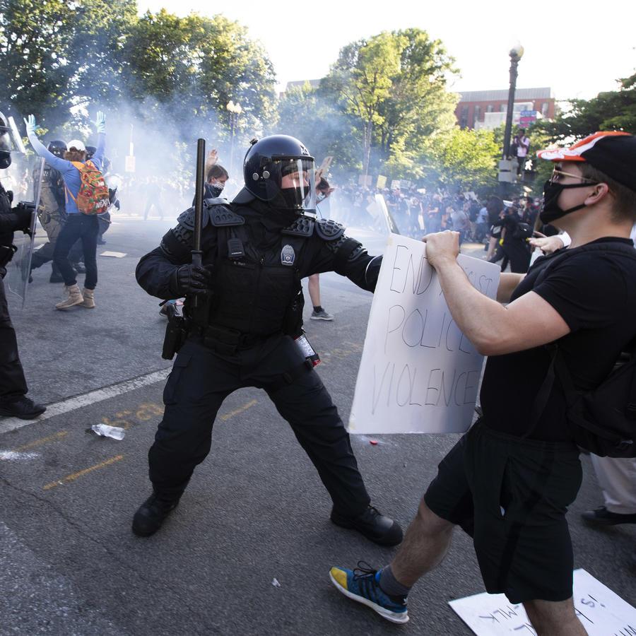 Un policía se enfrenta a un manifestante frente a la Casa Blanca en las protestas por la muerte de George Floyd.