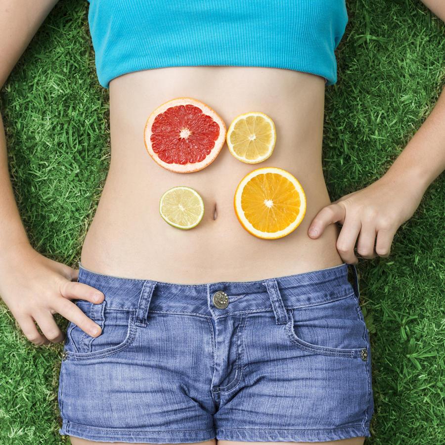 Mujer con frutas sobre su abdomen plano