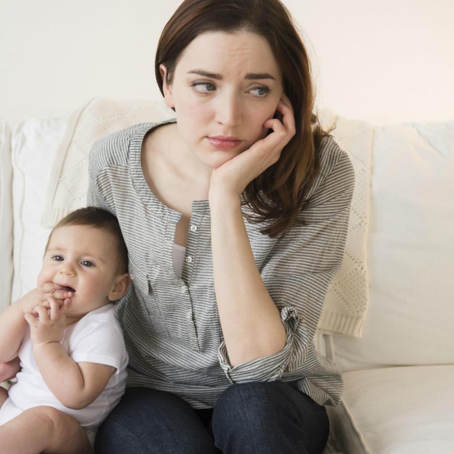 Mujer pensativa sosteniendo a su bebé