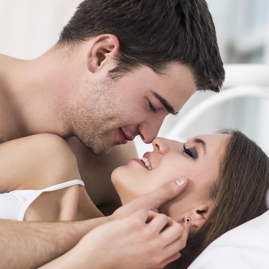 Pareja besándose en la cama