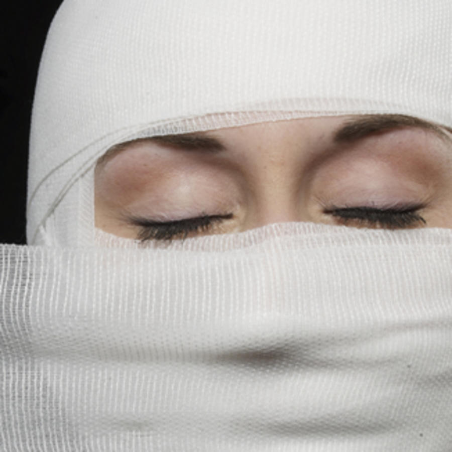 Woman's face being wrapped in bandages