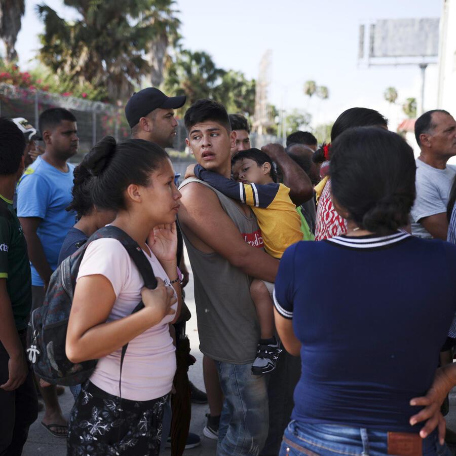 Migrantes hacen fila en Matamoros, México.