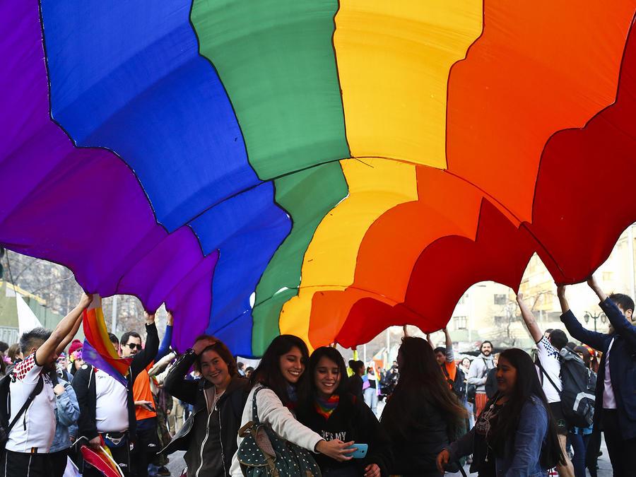 Una pareja se fotografía bajo una bandera de arcoiris durante una marcha de la comunidad LGBT en Santiago.