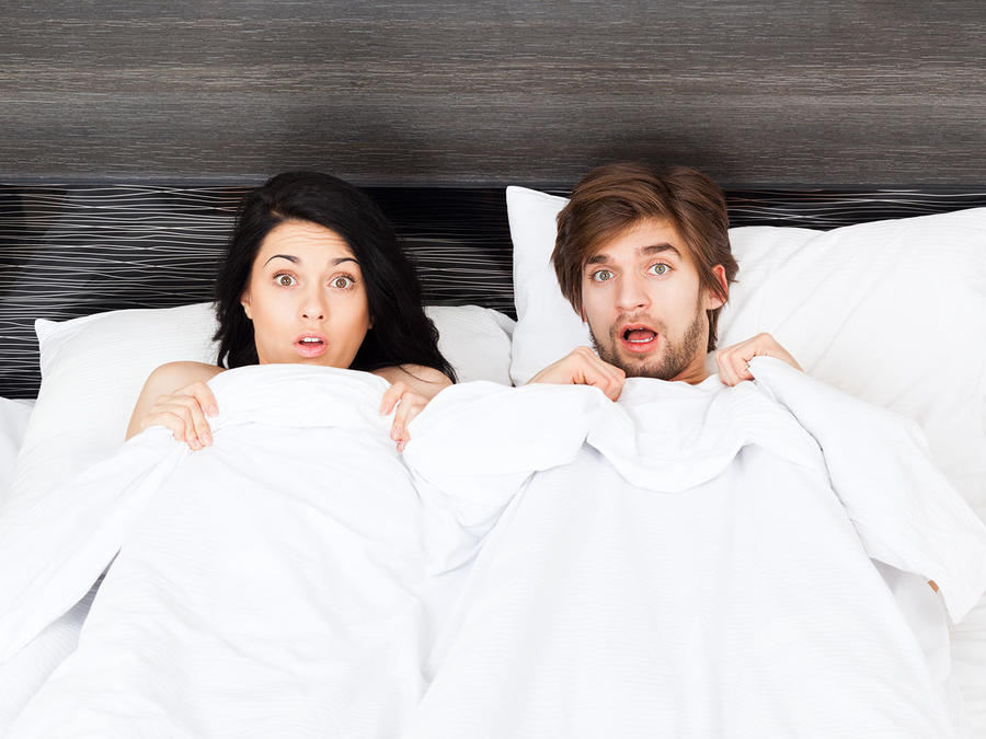 Pereja asustada en la cama