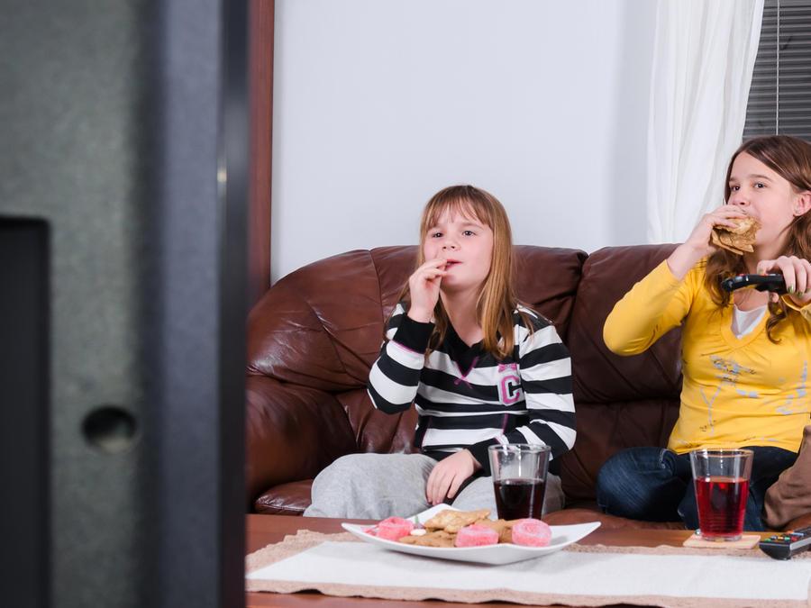 Niñas comiendo frente del televisor