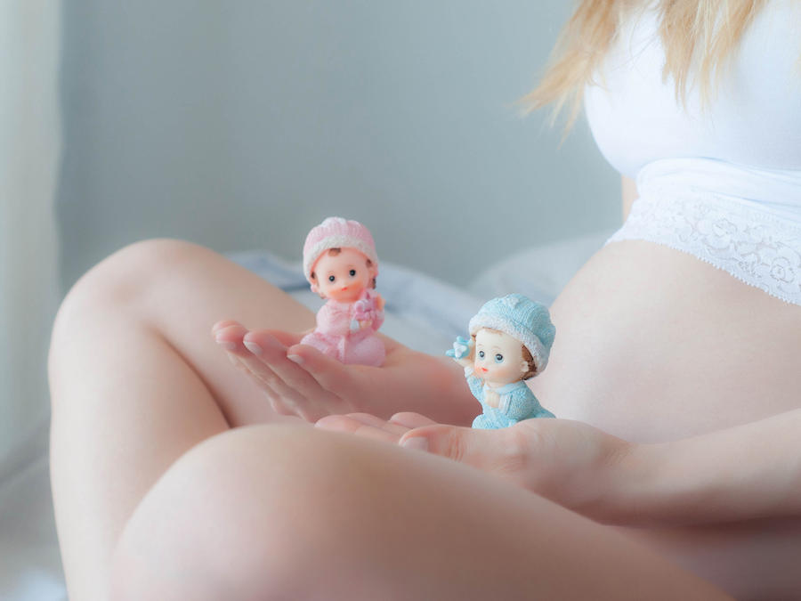 Mujer embarazada aguanta muñecos de bebés