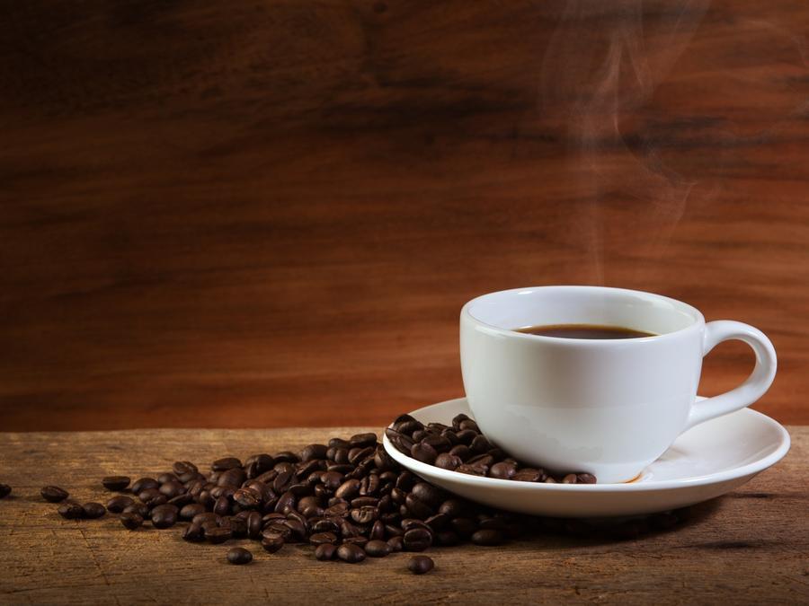 Café humeante en taza blanca al lado de taza de café