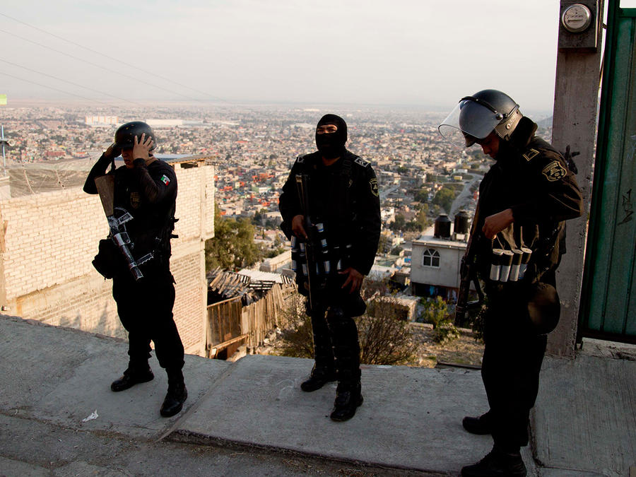 En esta foto del 19 de de enero de 2015, los agentes de policía se preparan para una operación de seguridad en Ecatepec, un barrio en las afueras de la Ciudad de México. El papa en su visita México celebrará una misa en una explanada al aire libre