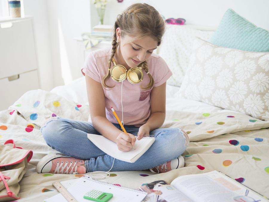 Preadolescente estudiando en su cuarto