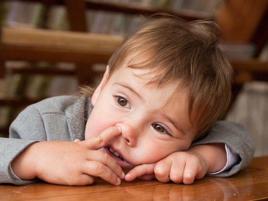 Niño con un dedo en la nariz