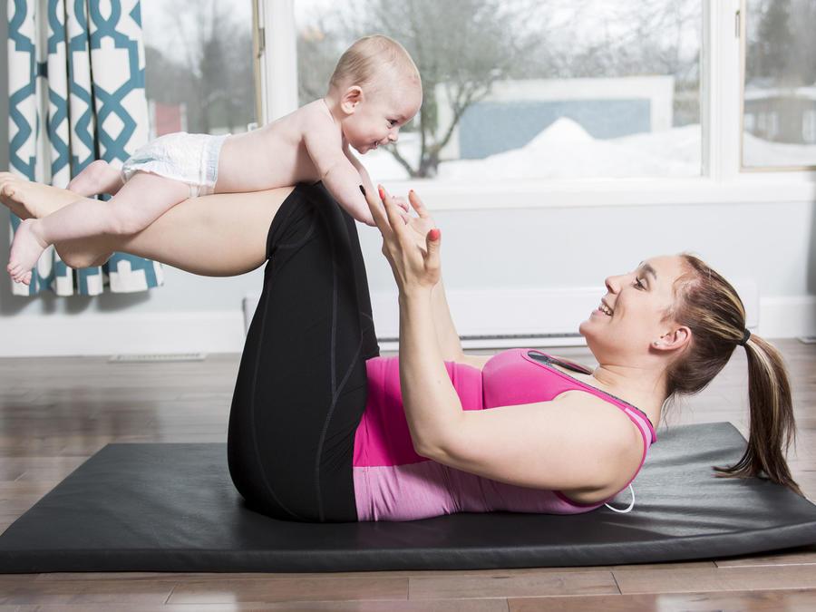 Mamá haciendo abdominales con su bebé en las piernas