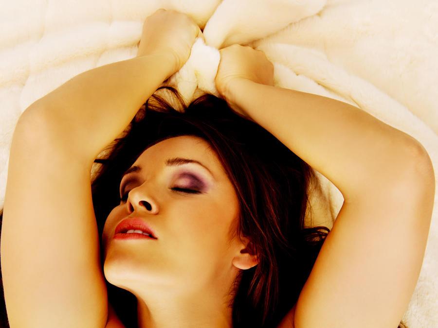 Mujer apretando sábanas al tener orgasmo