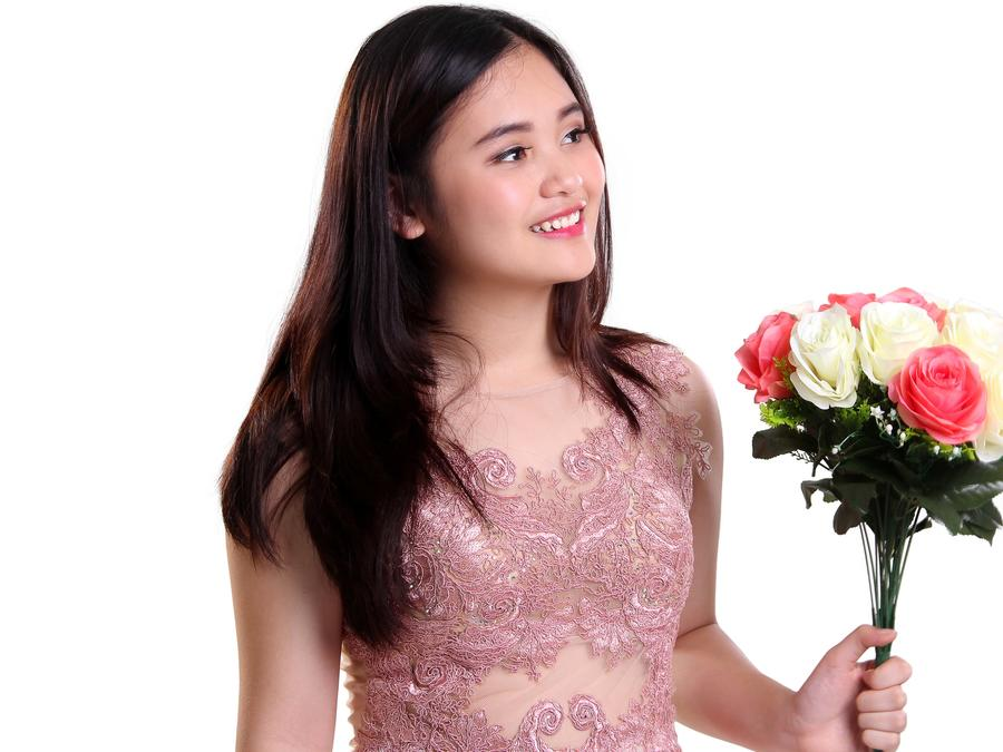 Joven con vestido rosado y ramo de flores