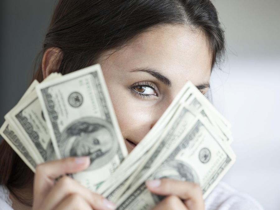 Mujer ocultándose tras billetes