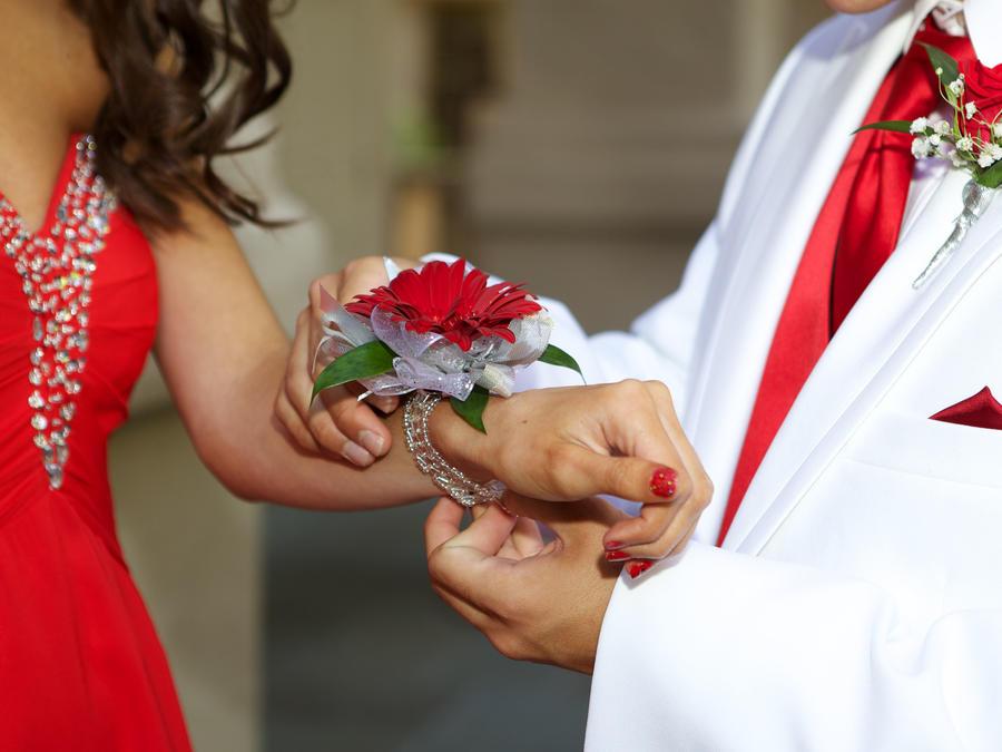 Chico le pone flor en la mano a chica antes del baile de graduación