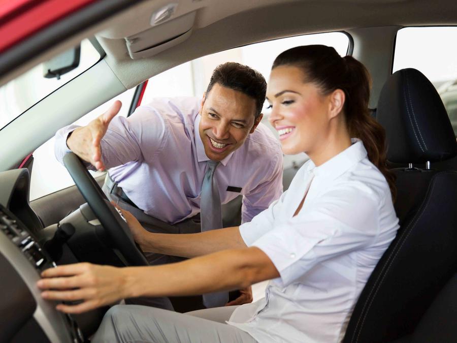 Vendedor en concesionario mostrandole un carro a una mujer