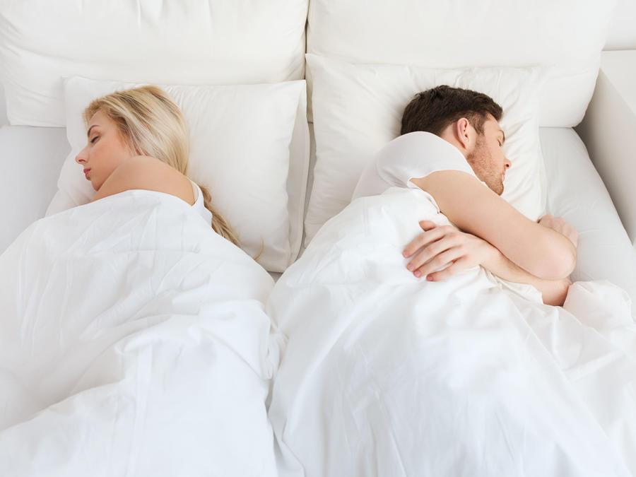 Pareja durmiendo en cama con sábanas blancas