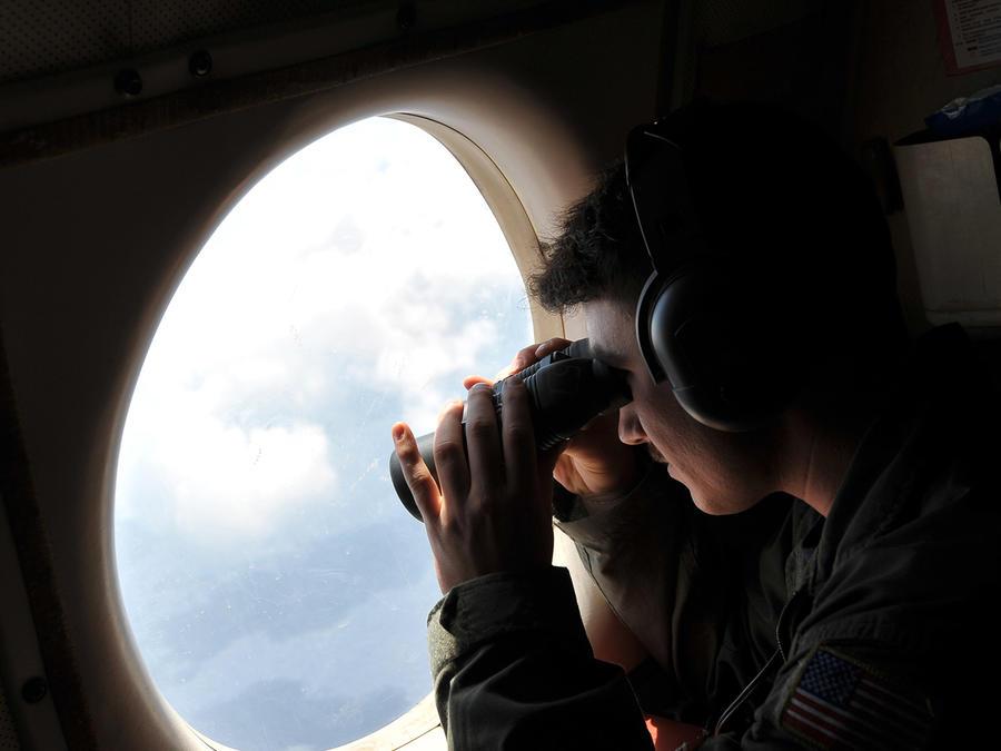 El teniente de la Marina estadounidense JG Dylon Porlas utiliza prismáticos para mirar por la ventana del avión de patrulla P-3C tras despegar Sigonella, Sicilia, el domingo 22 de mayo de 2016.
