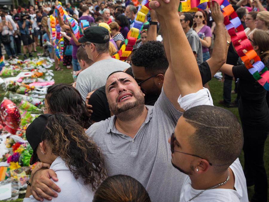 José Hernández (de gris) levanta la mano con su amigo Victor Bayez mientras lamentan la pérdida de sus amigas Amanda Alvear y Mercedez Flores durante una vigilia