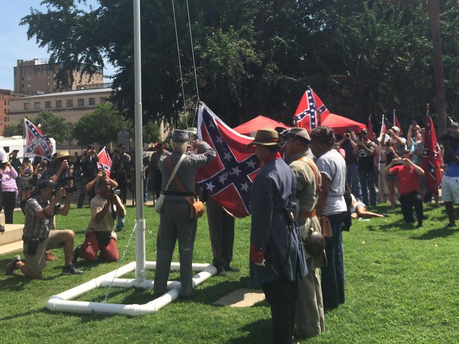 Partidarios de la bandera confederada la izan de manera temporal en un asta de los terrenos del Palacio Legislativo, en Columbia, South Carolina, el domingo 10 de julio de 2016