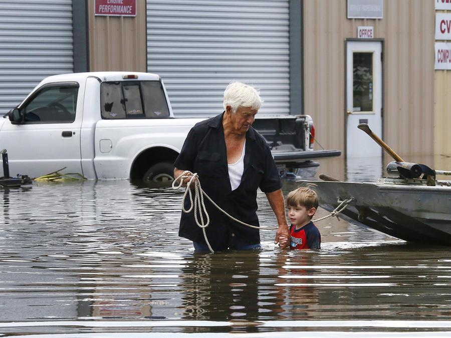 Un hombre con su bisnieto en las calles inundadas en Amant, Louisiana el Lunes 15 de Agosto del 2016