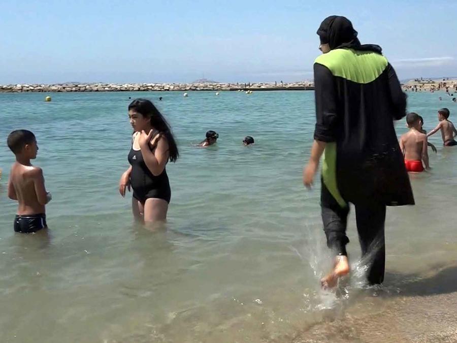 mujer con burnkini en la playa