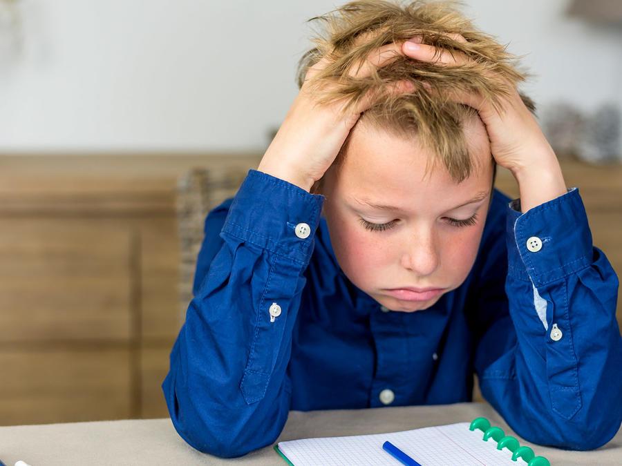 Niño estresado haciendo tarea