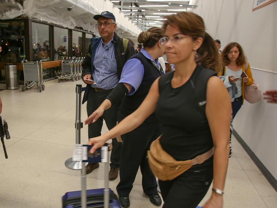 Un agente de policía monta guardia mientras los pasajeros esperan en la Terminal 7 del aeropuerto internacional de Los Ángeles, el domingo 28 de agosto de 2016.
