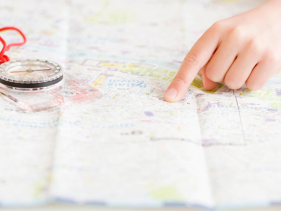 Dedo señalando mapa de Estados Unidos junto con brújula