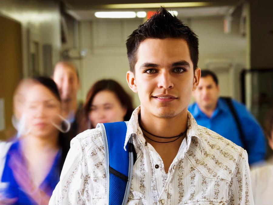 Joven latino en pasillo de la universidad