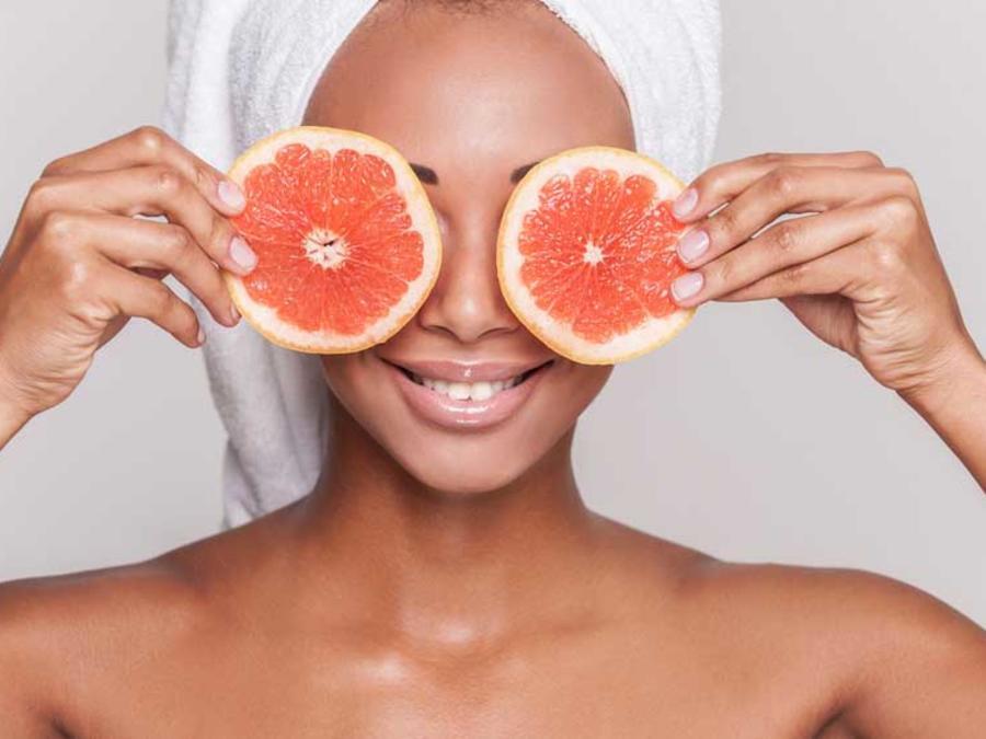 Mujer con rodajas de pomelo en los ojos