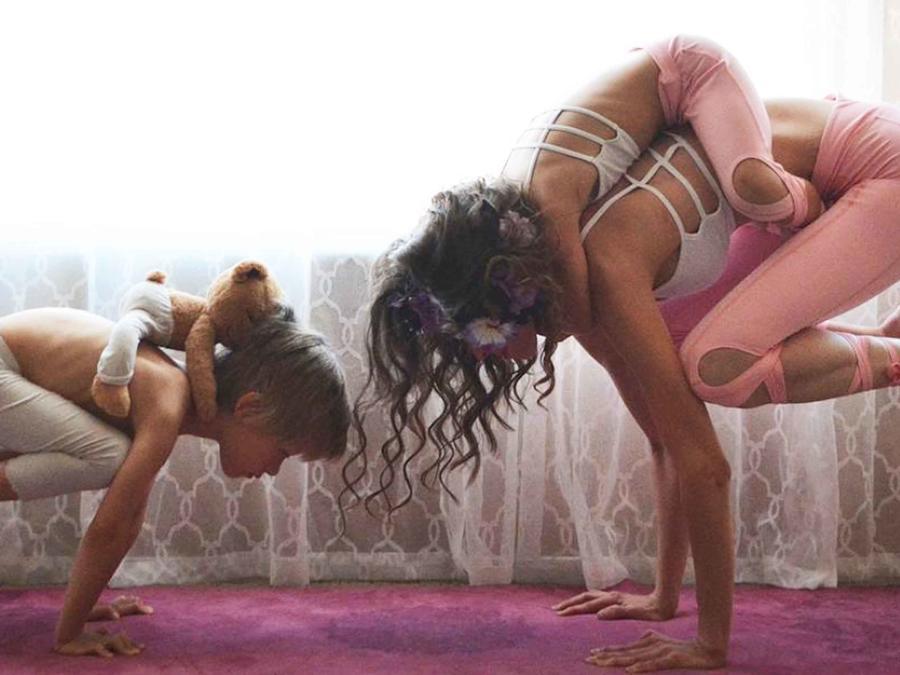 Mamá practicando yoga con sus hijos