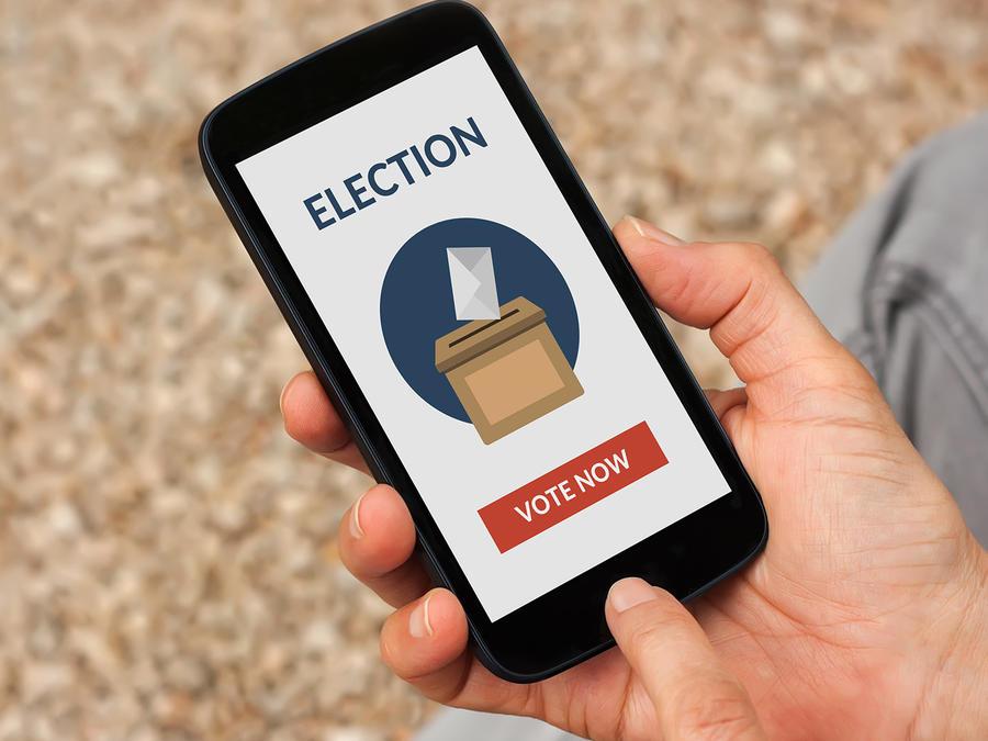 Manos sostienen Smartphone con imagen de elecciones