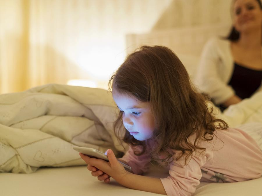 Niña en la cama usando smartphone