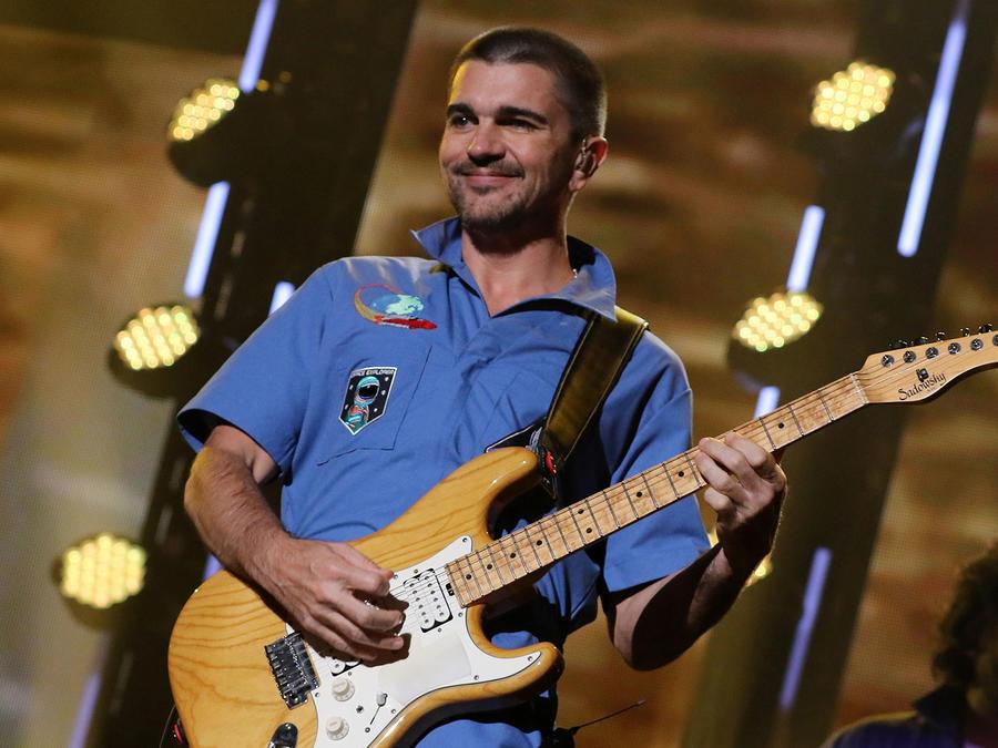 Juanes cantando y tocando guitarra en iHeartRadio Fiesta Latina