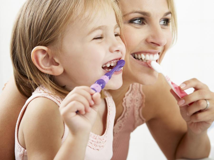 Madre e hija cepillándose los dientes en el baño
