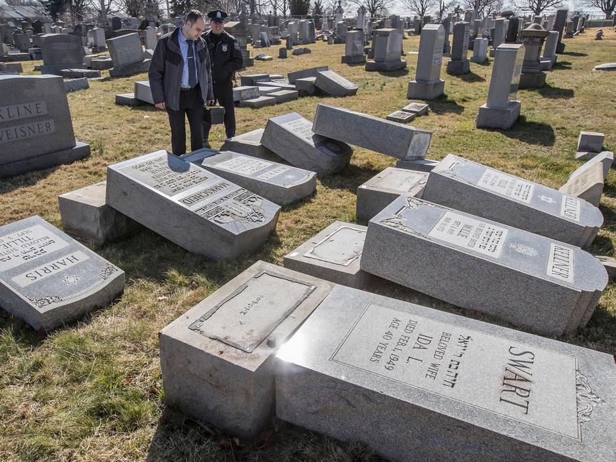 El detective Timothy McIntyre, del Departamento de Policía del Noreste de Filadelfia, y otro agente revisan lápidas que fueron derribadas en el cementerio judío Mount Carmel, el domingo 26 de febrero de 2017, en Filadelfia. (Michael Bryant/The Philadelphi