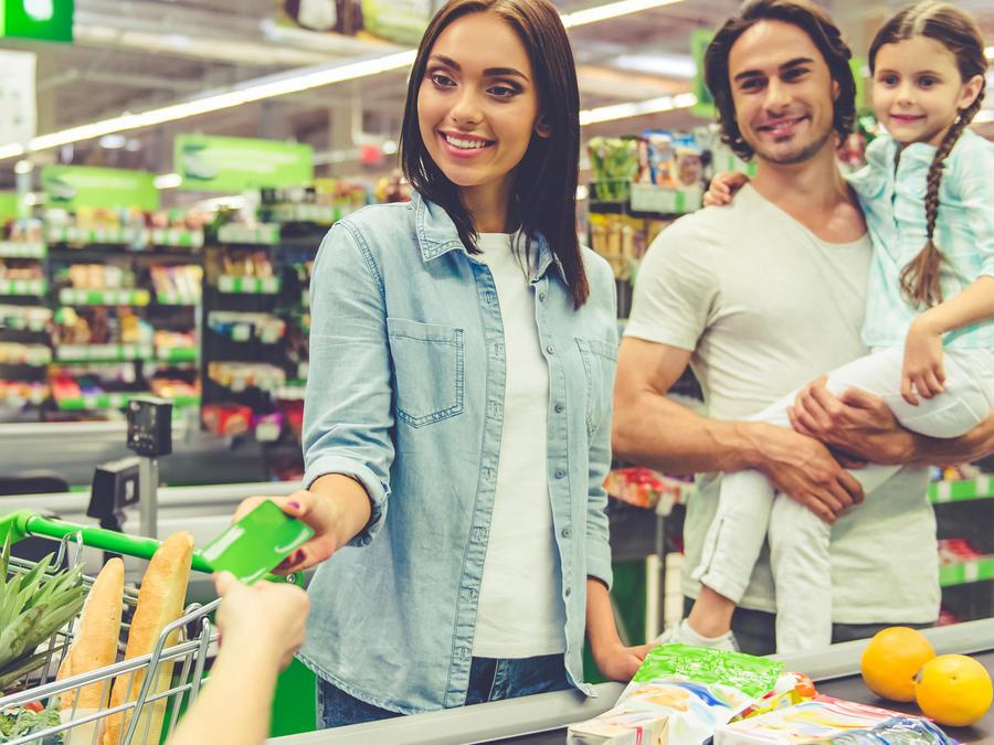 Mujer con su familia pagando las compras con tarjeta de crédito