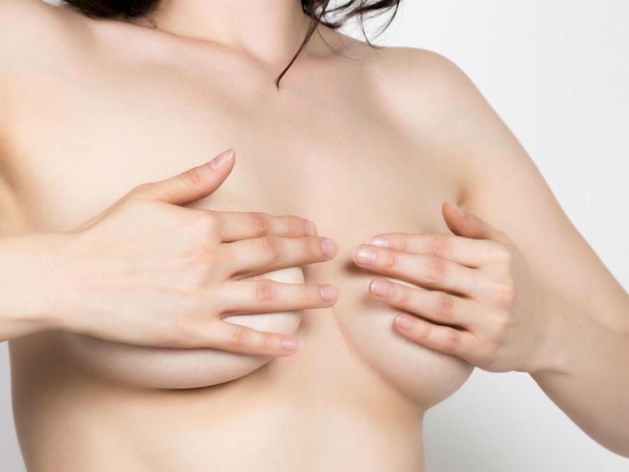 Mujer cubriendo sus pechos con sus manos
