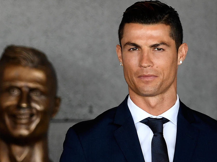 Cristiano Ronaldo posando con su busto