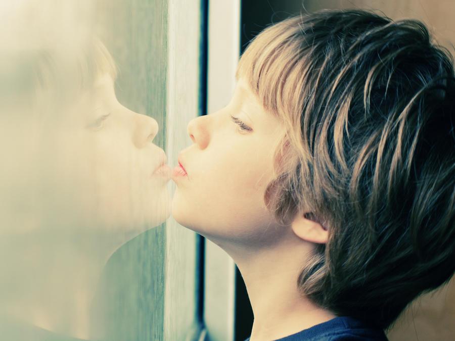Niño con autismo mirando por la ventana